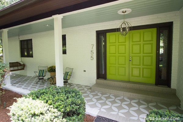 A front porch with a stenciled floor and a bright green door