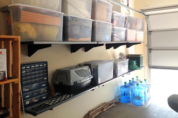 Plastic tubs on a wall organizer in a garage