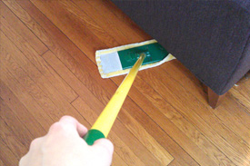 person uses dry mop to dust underneath a couch