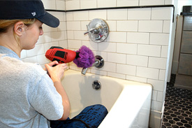 woman cleaning a bathtub faucet with a loofah and drill