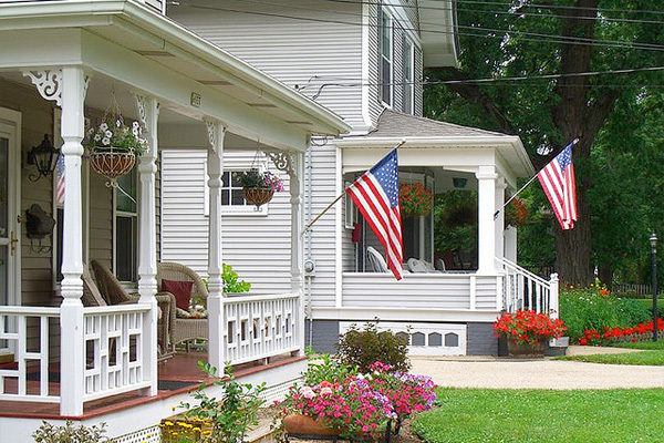 Image of American flags mounted on a porch.