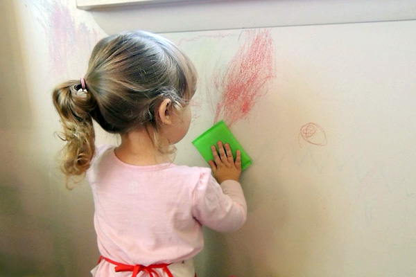 A child writing on a wall with crayon