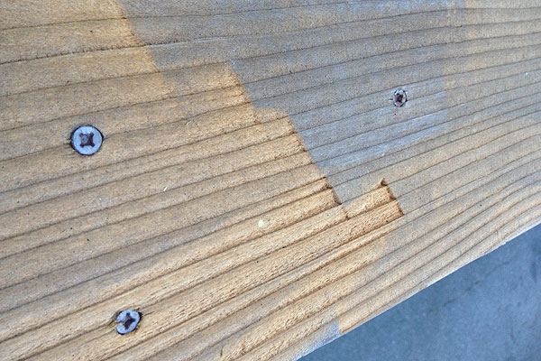 Power washer damage to a deck board