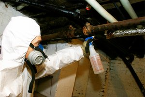 Man wearing protective suit removing asbestos from a home