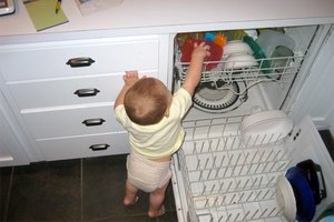 Toddler reaching into an open dishwasher