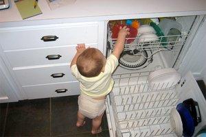 Toddler reaching into an open dishwasher
