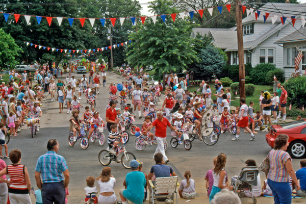 Kids riding bikes in a neighborhood Fourth of July parade