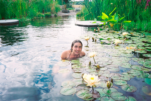 Woman swimming among lily pads in a natural pool