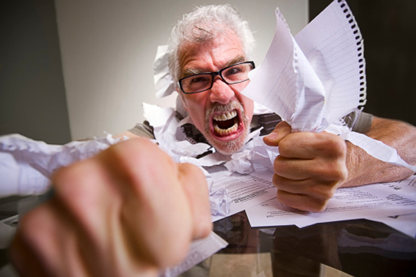 Upset man clutching paperwork