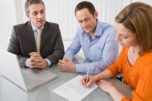 Couple doing paperwork with their REALTOR on a foreclosure