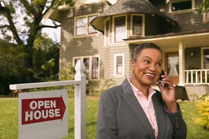 Woman standing next an open house sign in a yard