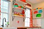 Fiesta ware displayed on open shelves in kitchen