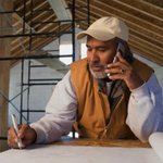 Contractor talking on telephone with client