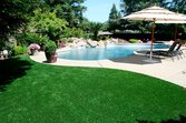 Synthetic lawn around a back yard pool