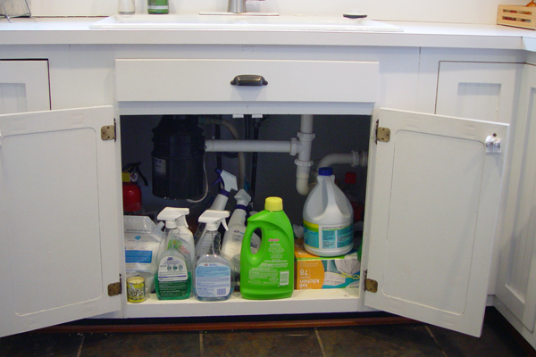 A too-full under-faucet kitchen cabinet
