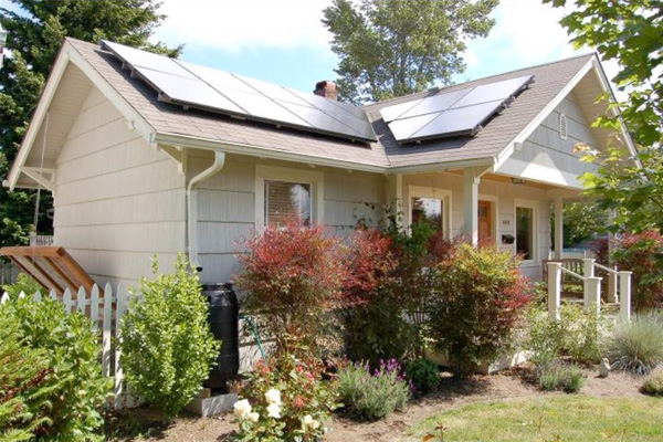A green home with solar panels and a rain barrel