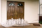 Sandbags piled next to front door of a home