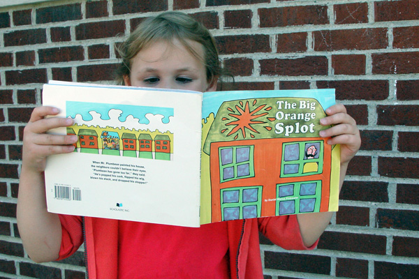 Liz's daughter reading The Big Orange Splot