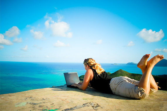 Woman Working on Laptop at a Beach | Home Office Deductions