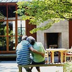 Older couple hugging outside house