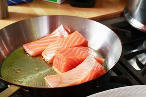 Salmon cooking on stove at home