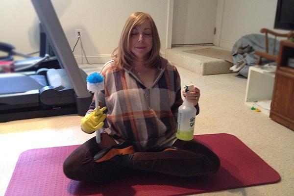 Lisa Kaplan Gordon in lotus position with cleaning supplies