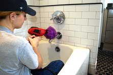 Cleaning a bathtub with a loofah attached to a drill
