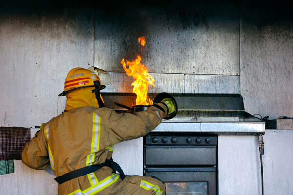 Firefighter putting out a kitchen fire