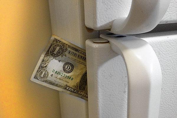 Dollar bill stuck in a refrigerator door