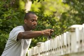 man-carefully-painting-fence-diy-getty2