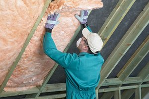 Man installing insulation in home attic