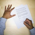 Man's hand signing construction contract
