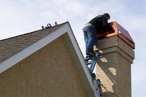 Man replacing chimney cap on house