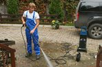 Man cleaning a patio with a power washer