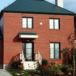 Exterior of red brick house with metal roof