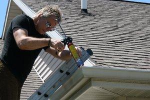 Gutter repair | Man fixing gutters on a house
