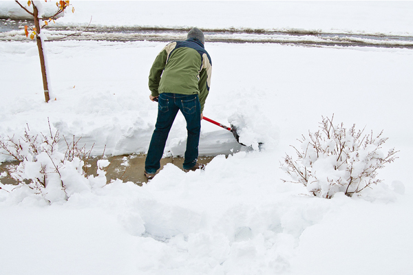 Person shoveling snow in a yard