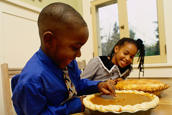 Child sticking his finger in a pumpkin pie