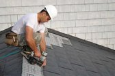 Man installing interlocking metal shingles
