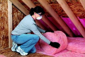 Woman unrolling insulation in attic